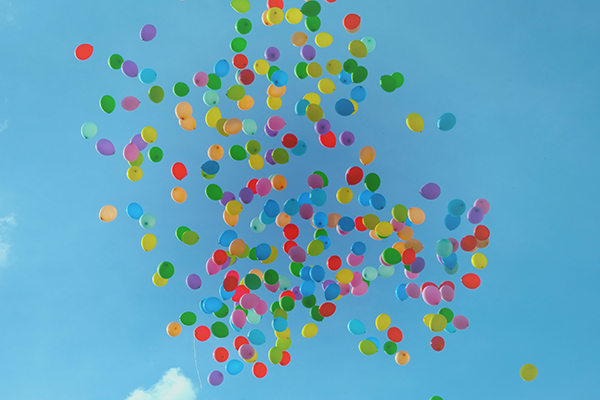 Lots of multi-coloured balloons floating in a beautiful blue sky - Create Health