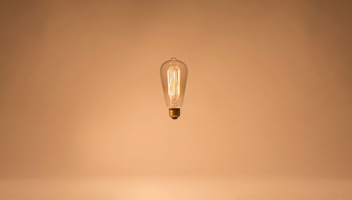 Lightbulb with intricate filament suspended - Create Health