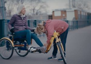 Lady sitting on a special bicycle with another lady buckling her foot - Mindset Science bicycle