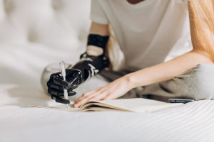 Girl sat on a bed and writing with a bionic arm - Med Tech